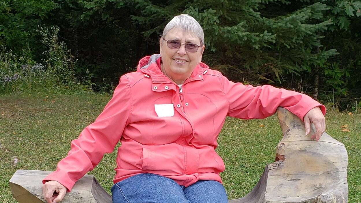 Une femme souriante assise sur un banc en bois devant une forêt.