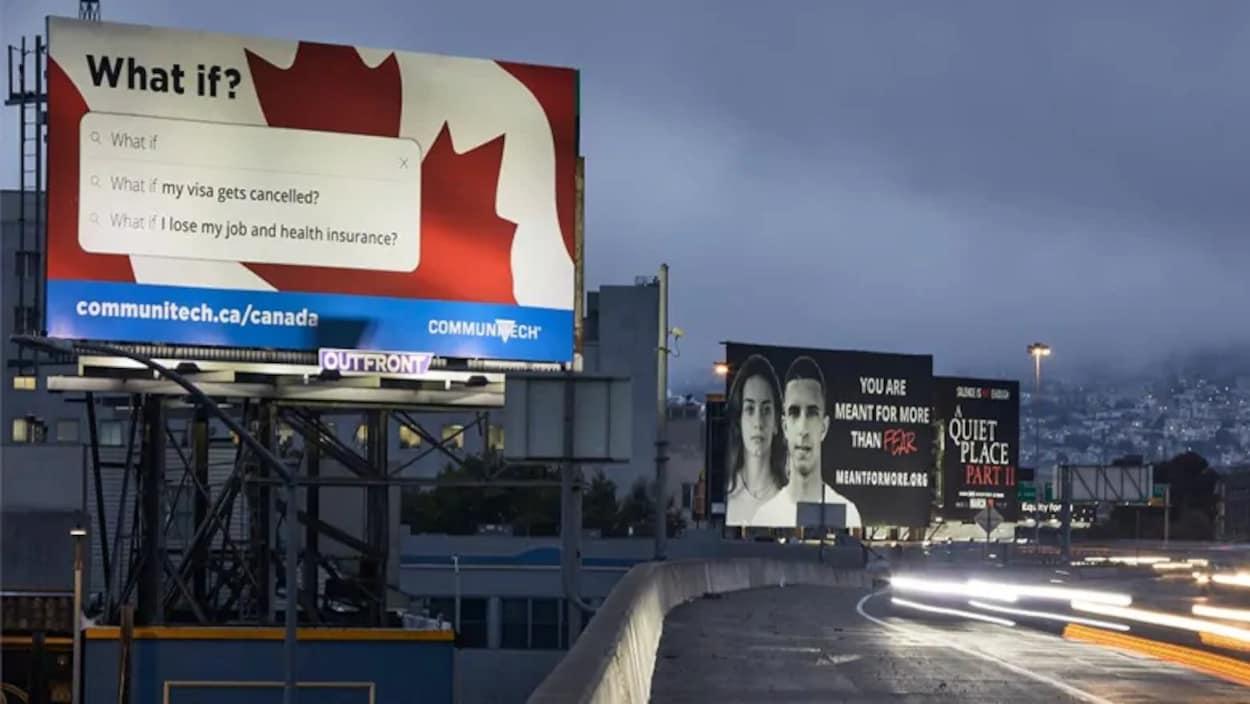 Un panneau publicitaire est éclairé au bord d'une autoroute.