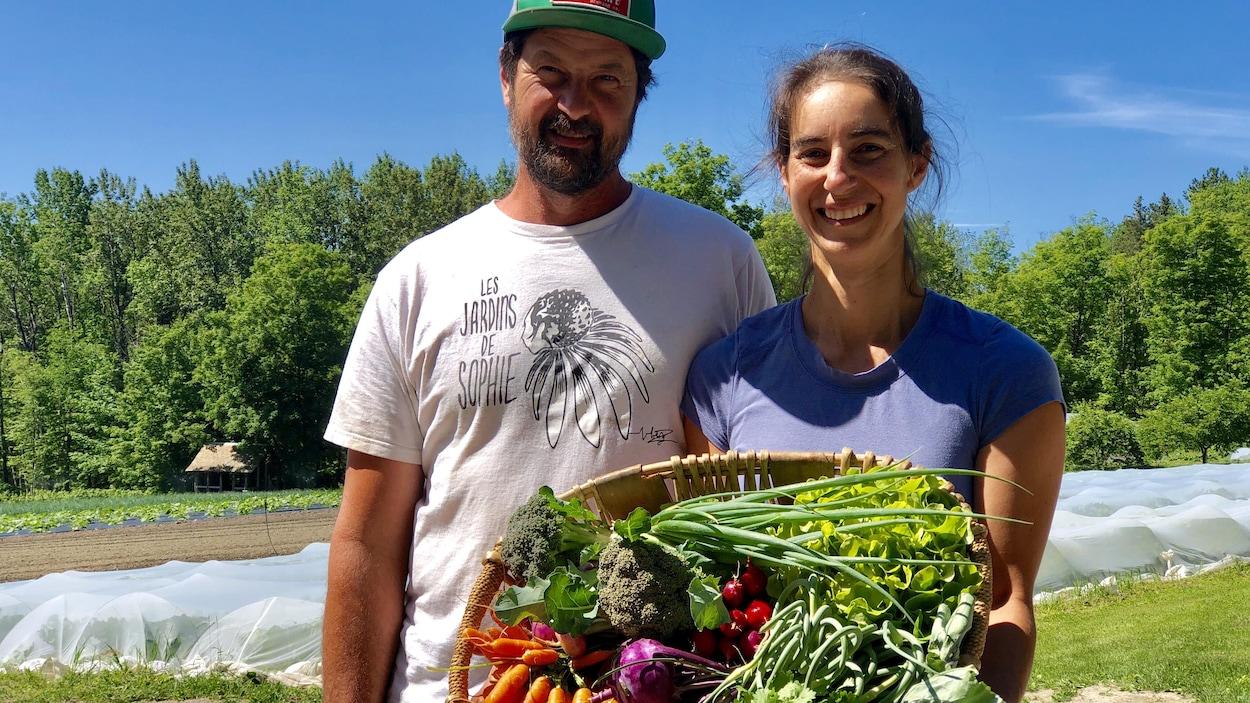 Les propriétaires des Jardins de Sophie tiennent un panier de légumes.