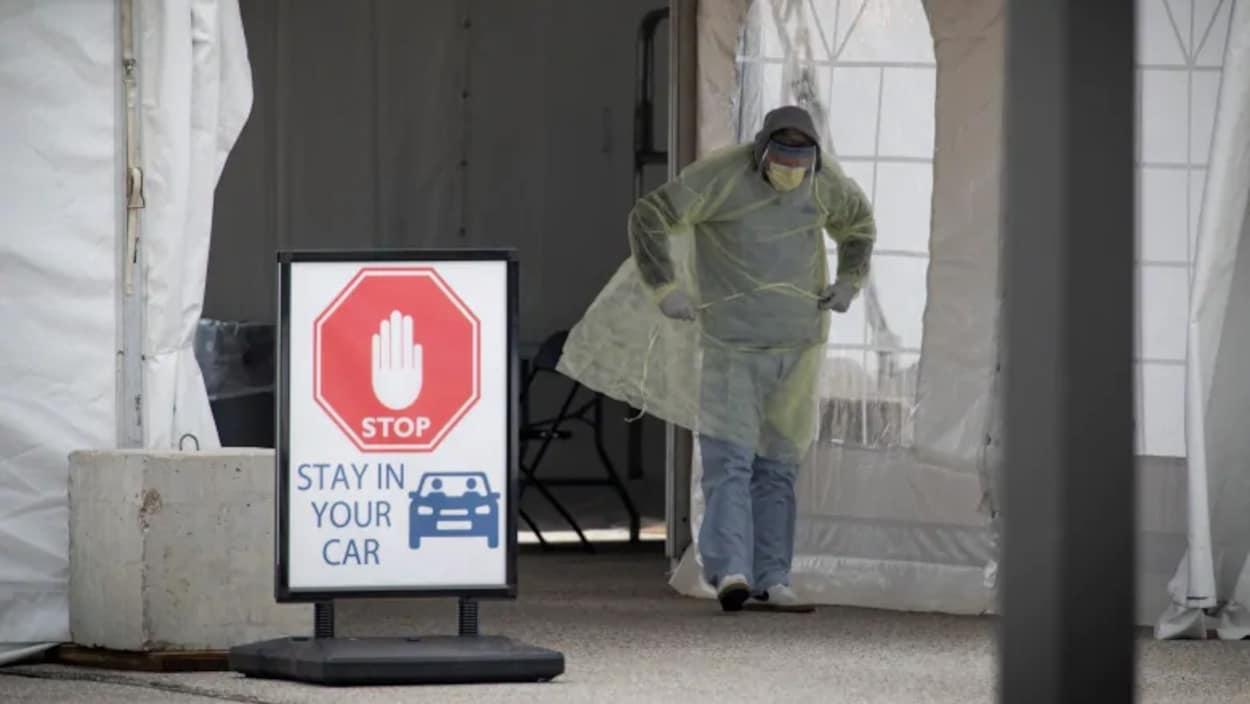 Un travailleur de la santé effectue des tests de COVID-19 au volant, dans une installation spécialement construite près de l'Hôpital général d'Etobicoke, à Toronto.
