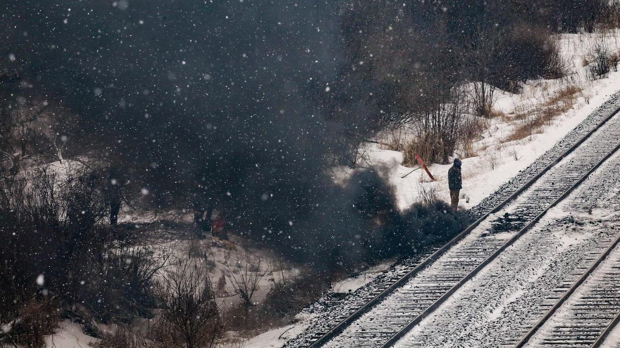 De la fumée noire sort d'un feu de pallettes de bois au bord d'une voie ferrée