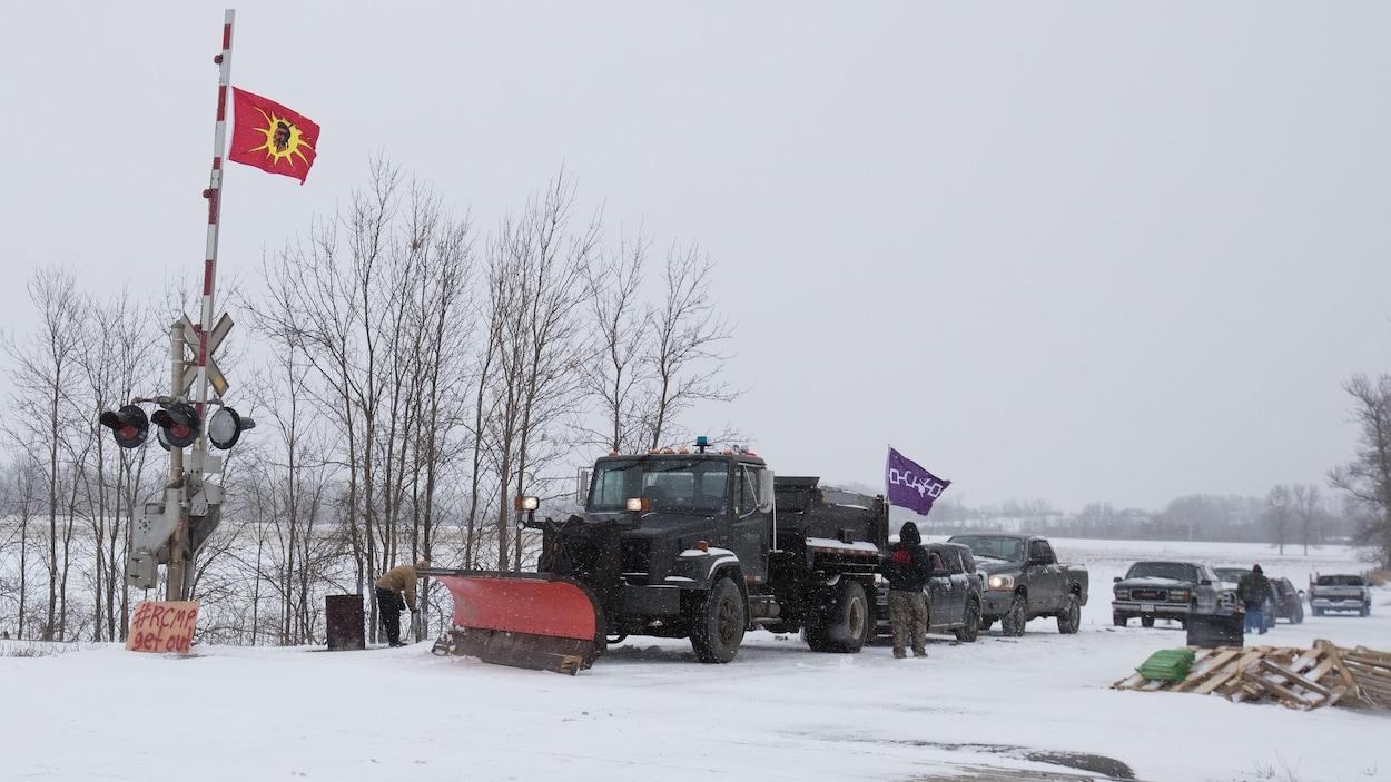 Un camion équipé d'une déneigeuse et d'autres véhicules stationnent devant une voie de chemin de fer. Plusieurs manifestants se trouvent sur le lieu.