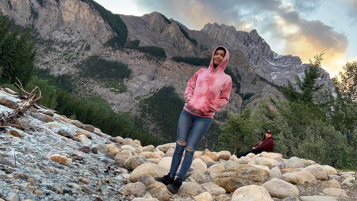 Dionne Durocher se tient sur des rochers devant une montagne.
