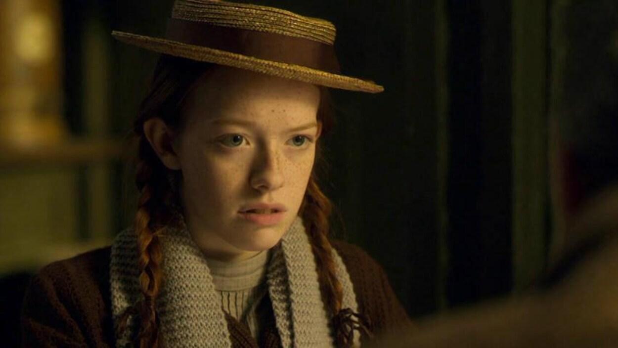 Anne porte un chapeau de paille orné d'un ruban brun et un foulard gris pâle.