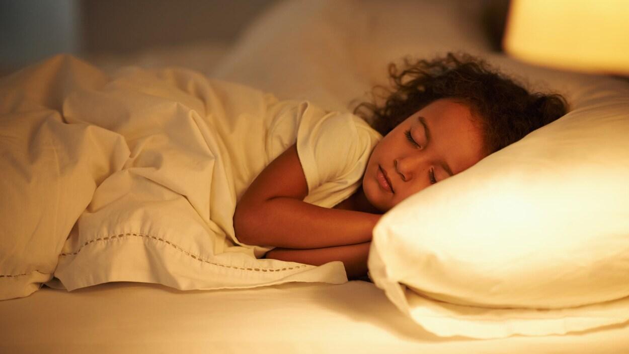 Une petite fille est endormie dans un lit.