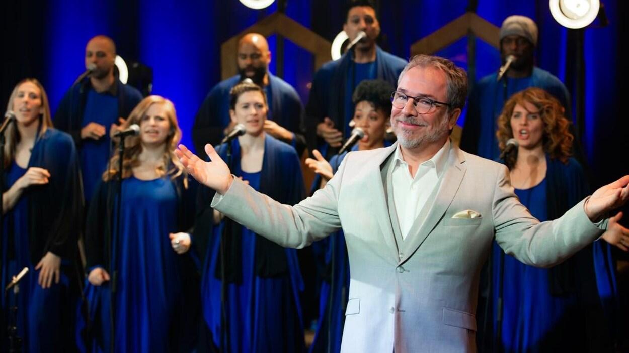 Christian Bégin pose les bras ouverts devant la chorale, dont les membres sont habillés en bleu.
