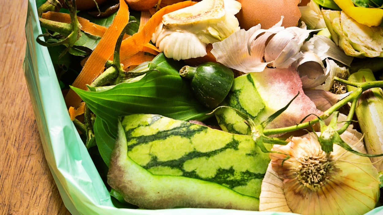 Sur une table en bois, un sac de plastique vert est rempli de résidus alimentaires.