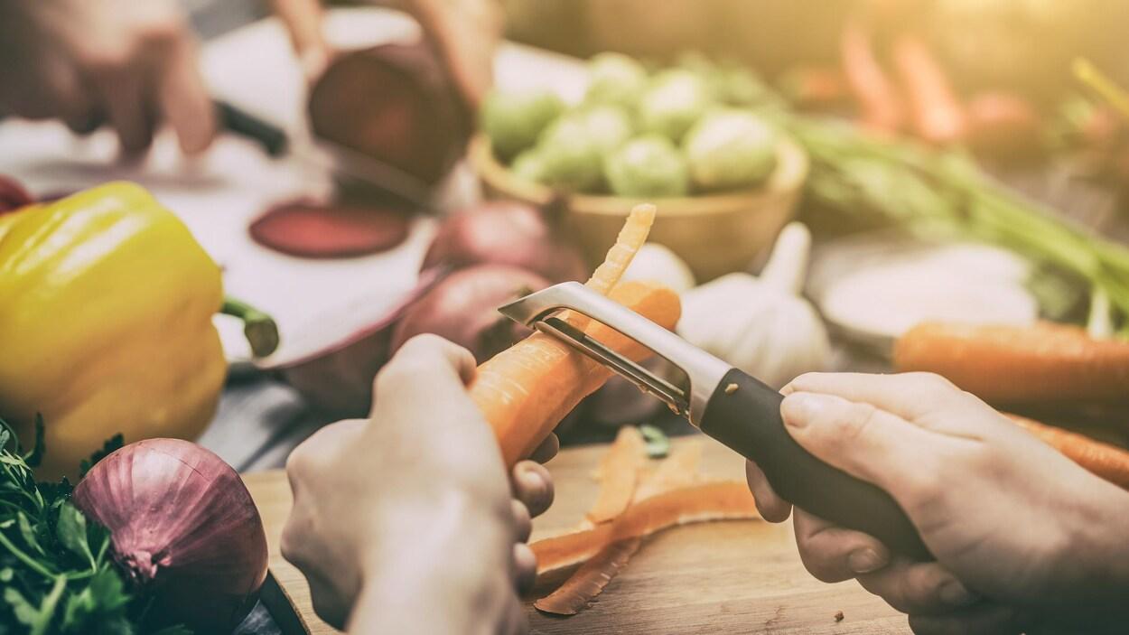 Une personne qui épluche une carotte sur un plateau de légumes.