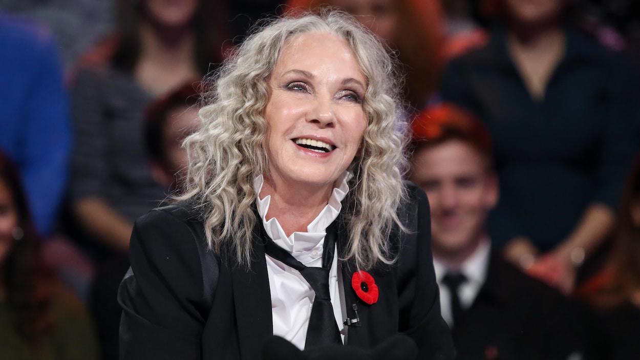 Elle porte une chemise blanche, une cravate noire et un veston noir sur un plateau de télévision. On voit un public derrière elle.