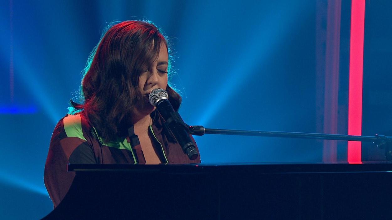 Elle chante au piano.