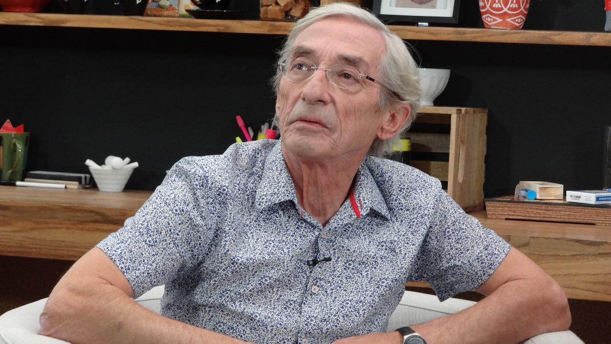 Assis dans le fauteuil, Richard Desjardins a un air sérieux en regardant une vidéo sur le moniteur.