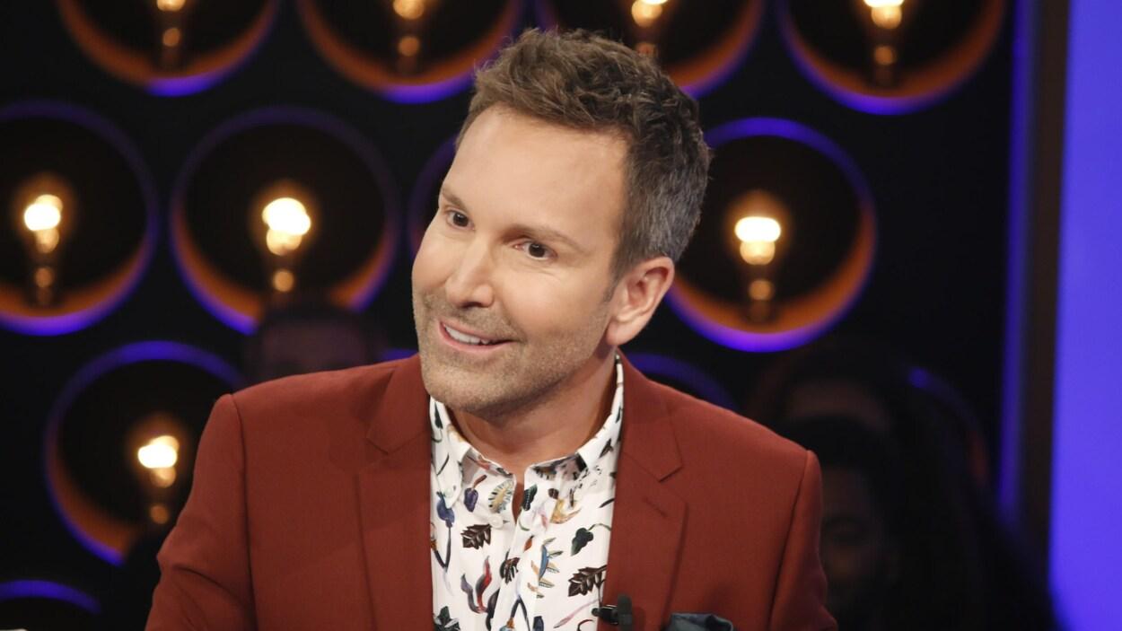 Éric Salvail porte une chemise à motifs et un veston.