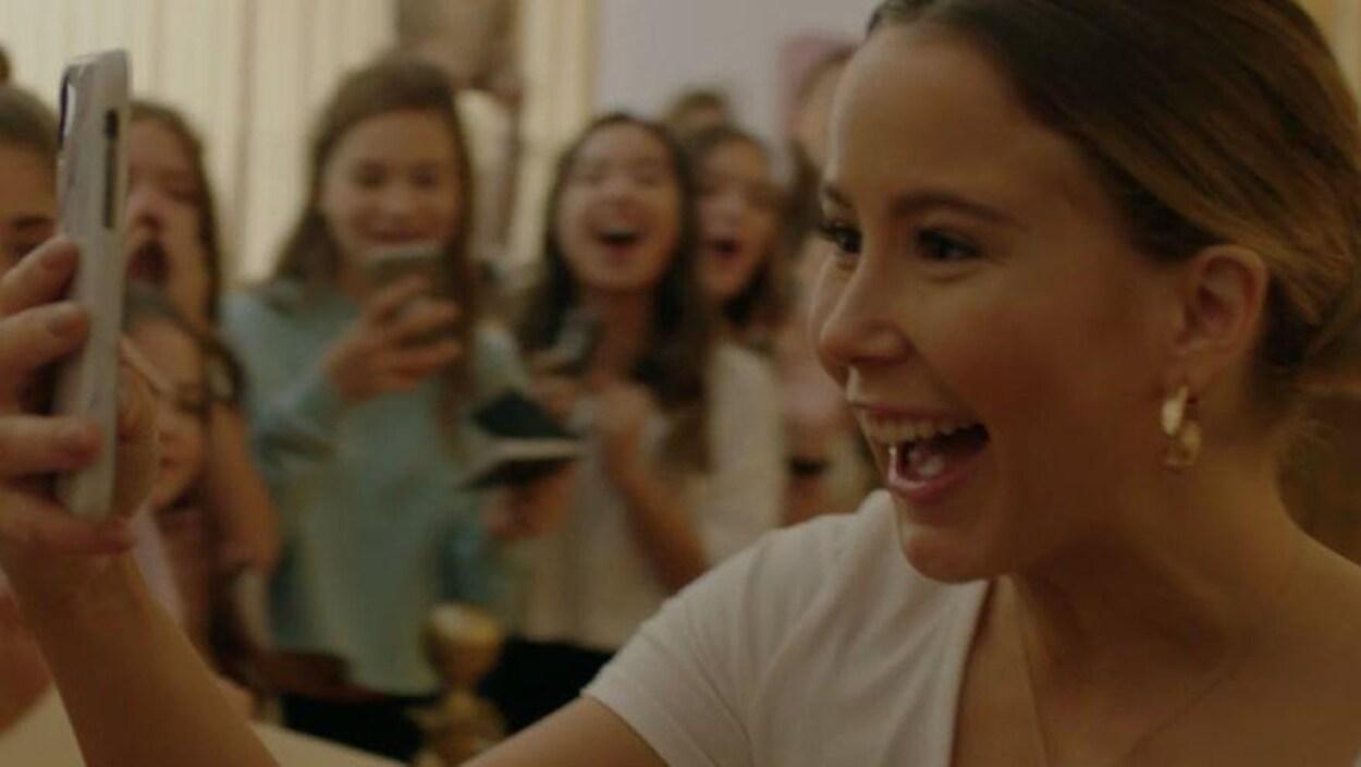 Une jeune femme (Juliette Gosselin), souriante, se prend en photo devant des admiratrices.