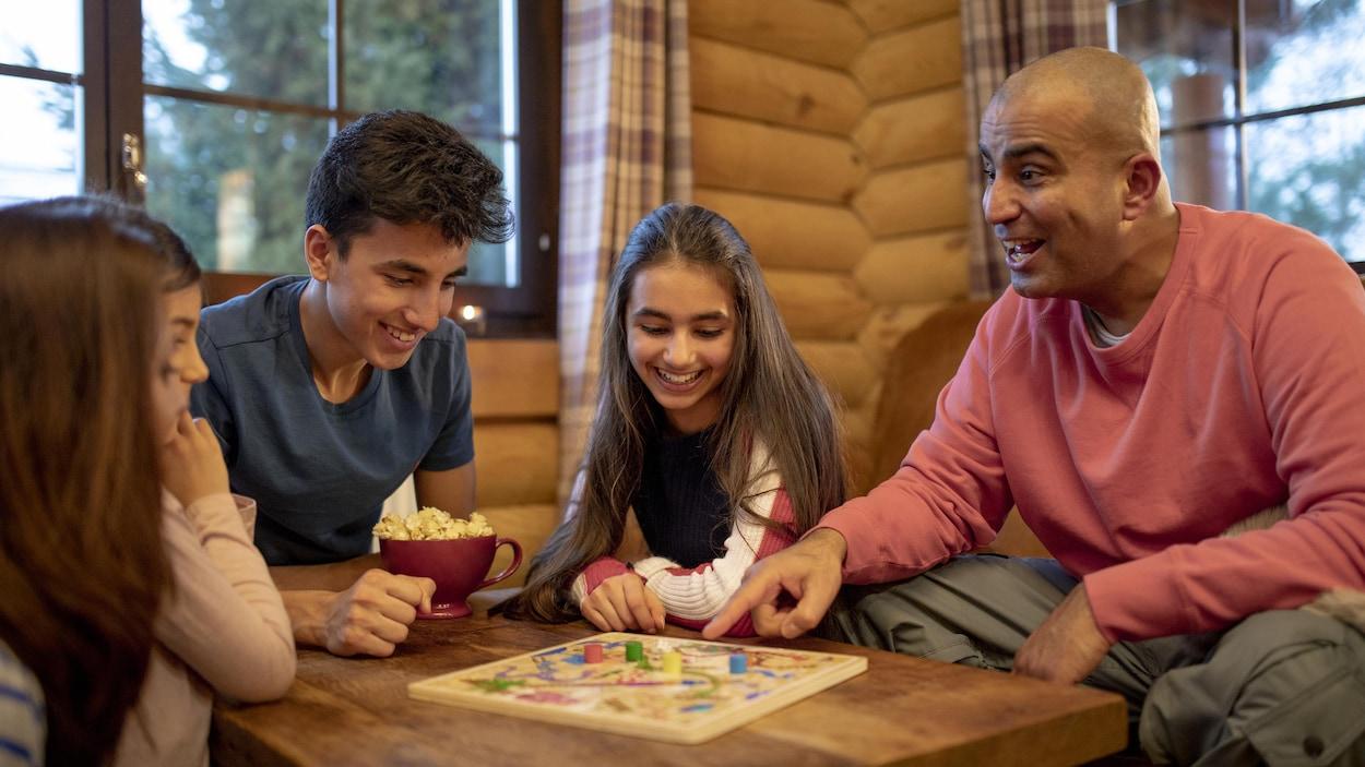 Une famille prend plaisir autour d'un jeu de société.