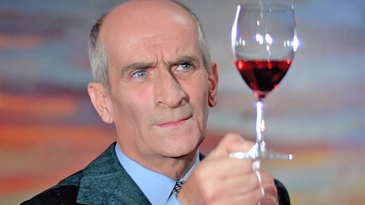 Un homme regarde un verre de vin rouge qu'il tient au bout de ses doigts.