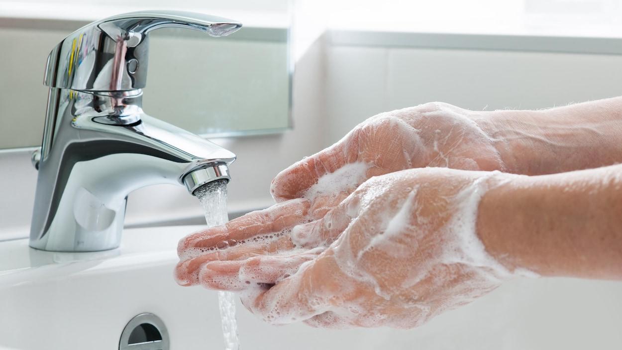 Gros plan sur des mains qui sont pleines de savon sous un robinet.