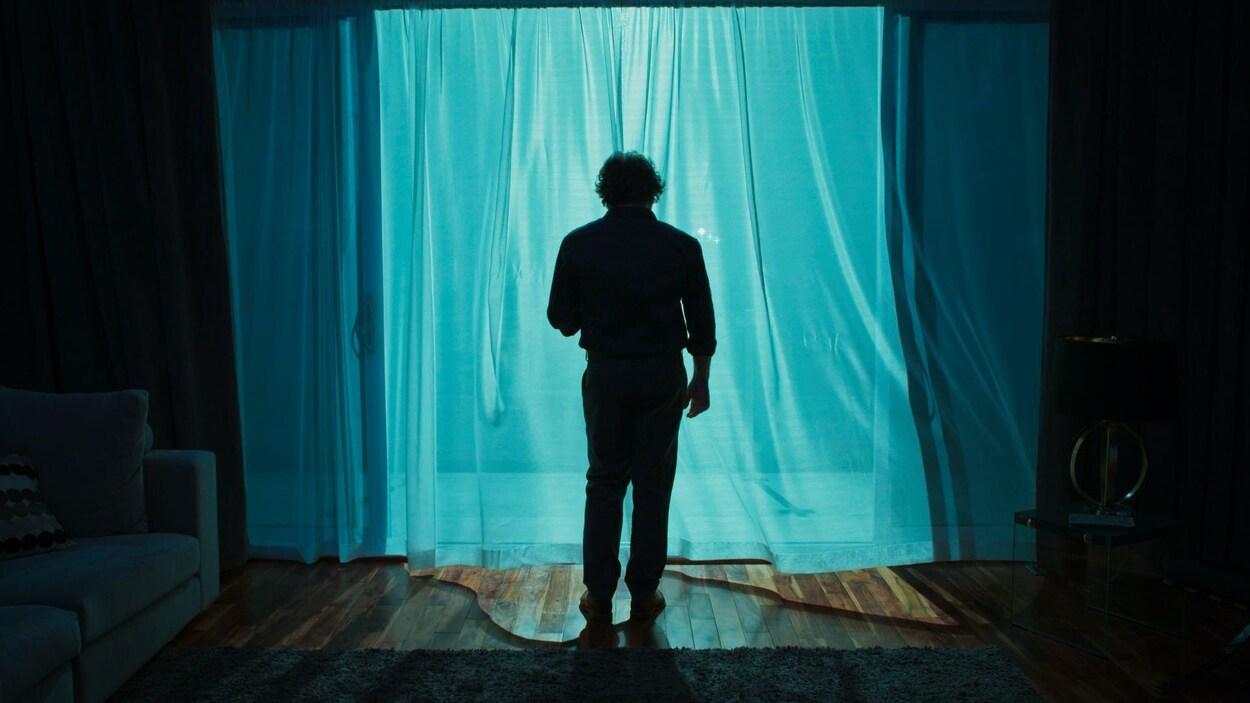 Un homme de dos, debout devant sa fenêtre et un rideau qui vole au vent