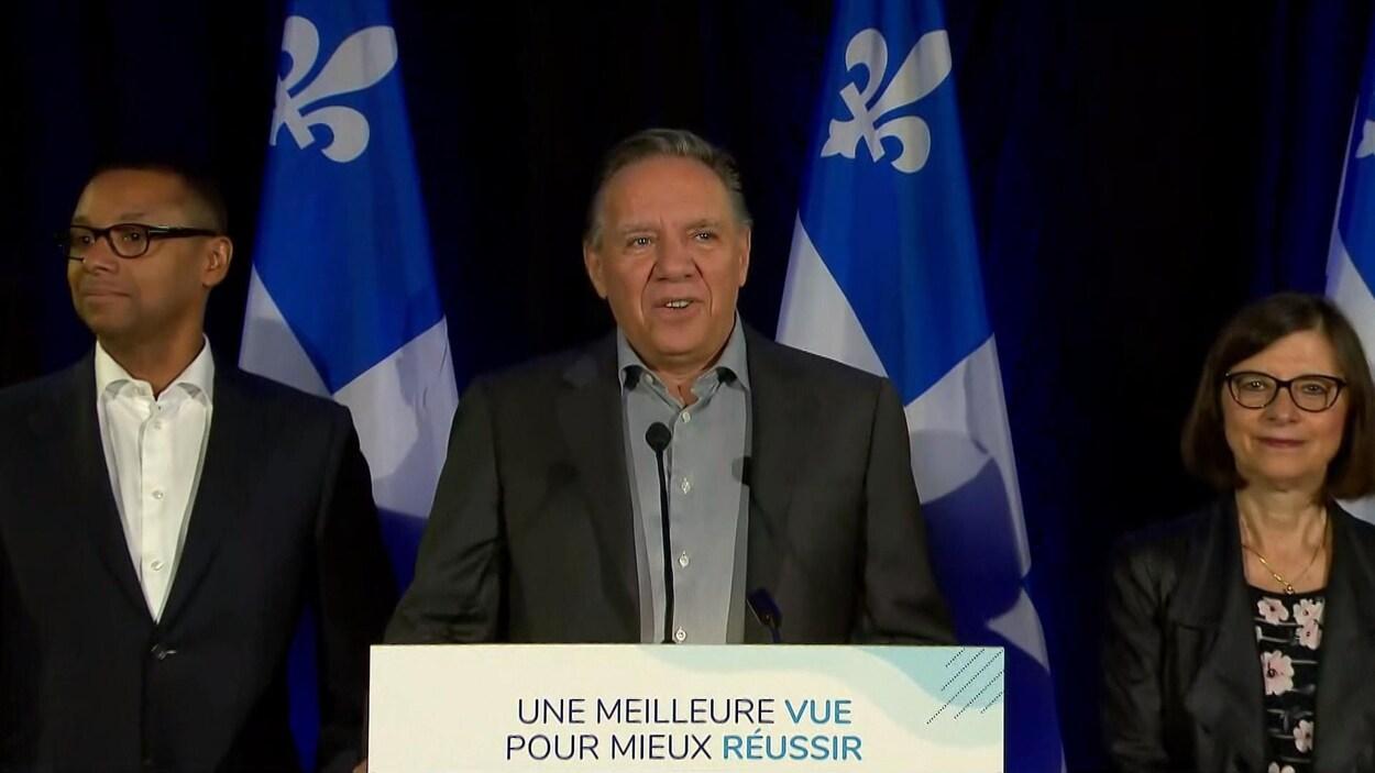 François Legault se dresse, avec deux ministres, devant un lutrin où il est écrit : «Une meilleure vue pour mieux réussir».
