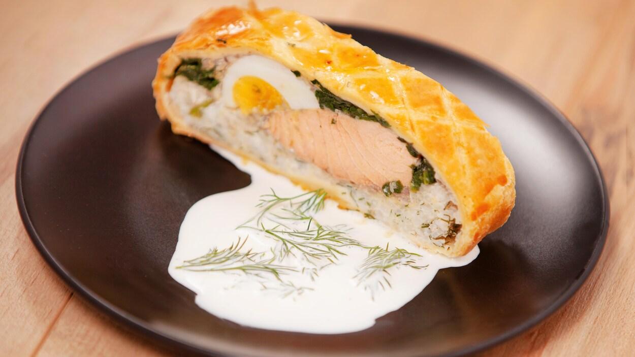 Un koulibiac servi sur une assiette ronde accompagné d'une sauce blanche.
