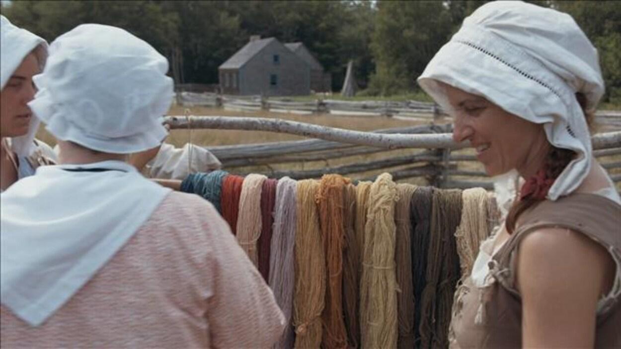 Des femmes en habits d'époque devant un séchoir à laine.
