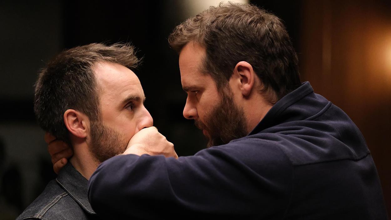 Un homme (Antoine Bertrand) la main posé sur la bouche d'un autre homme (Louis-José Houde) qu'il tient par le cou.