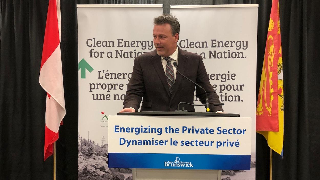 Mike Holland, ministre de l'Énergie, fait un discours.