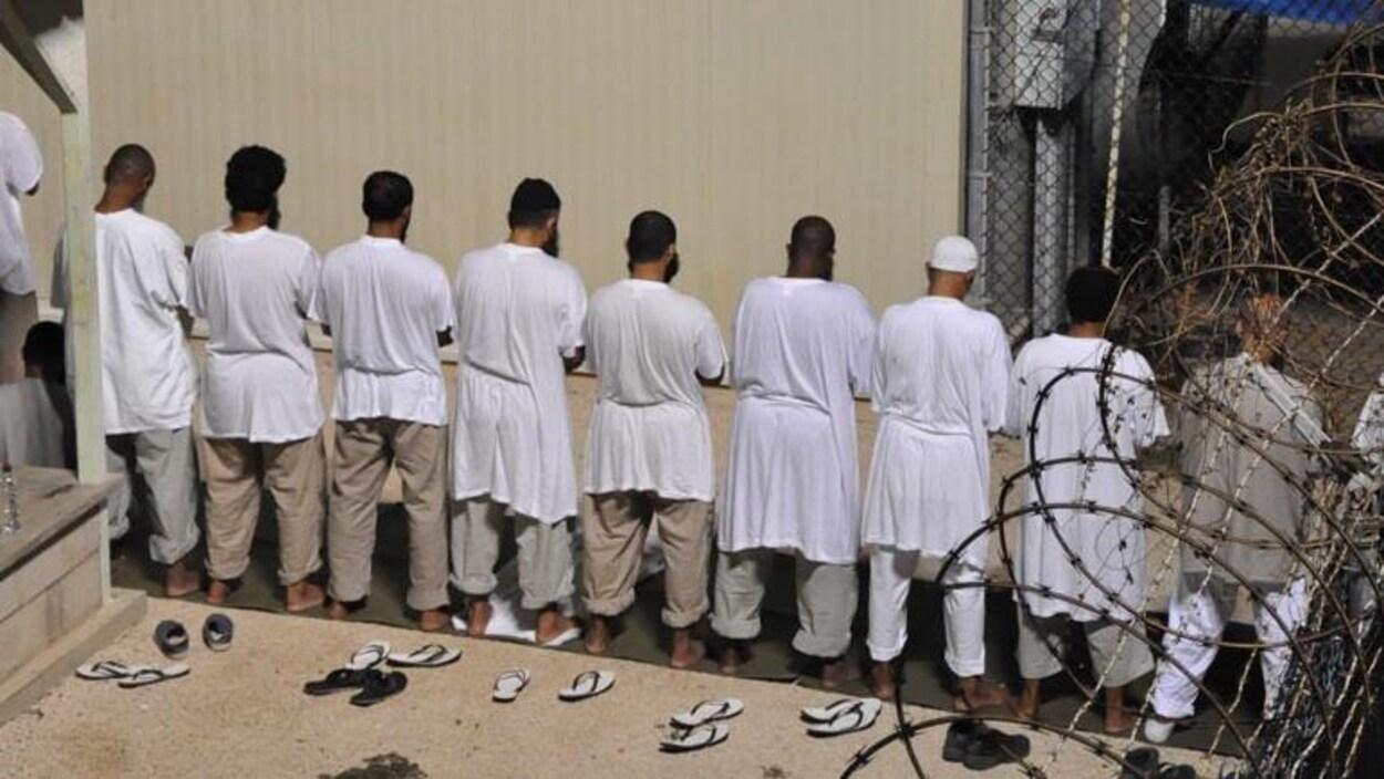 Des prisonniers, en blanc, de dos, en train de prier.