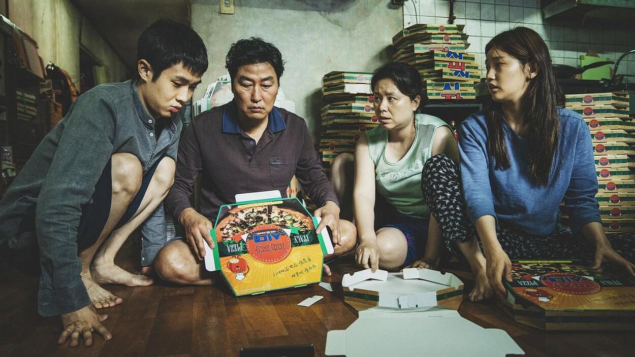 Une famille de quatre assise par terre, autour d'un carton de pizza.