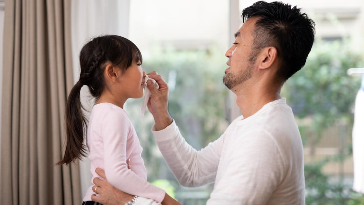 Un père mouche sa petite fille.