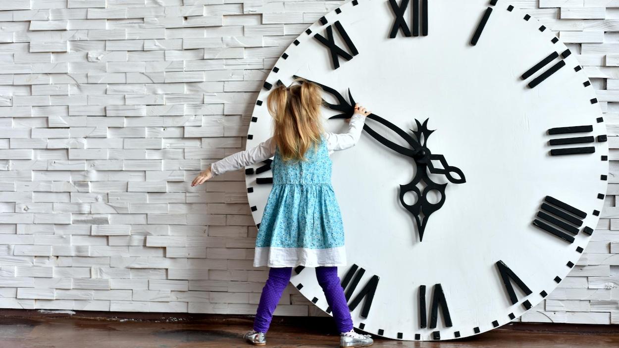 Une petite fille fait tourner l'aiguille d'une horloge surdimensionnée.