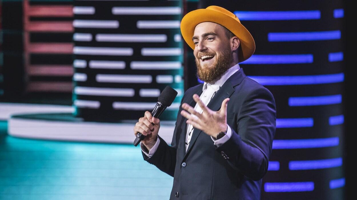 Il est sur scène en veston avec un chapeau orange.