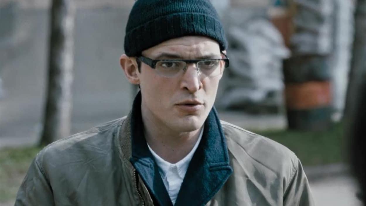 Un homme (Niels Schneider) portant un bonnet et des lunettes en plan moyen.