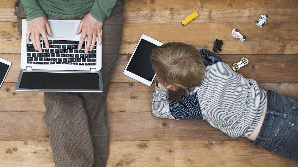 Une mère et son fils installés sur le plancher avec une collation, un ordinateur et une tablette.