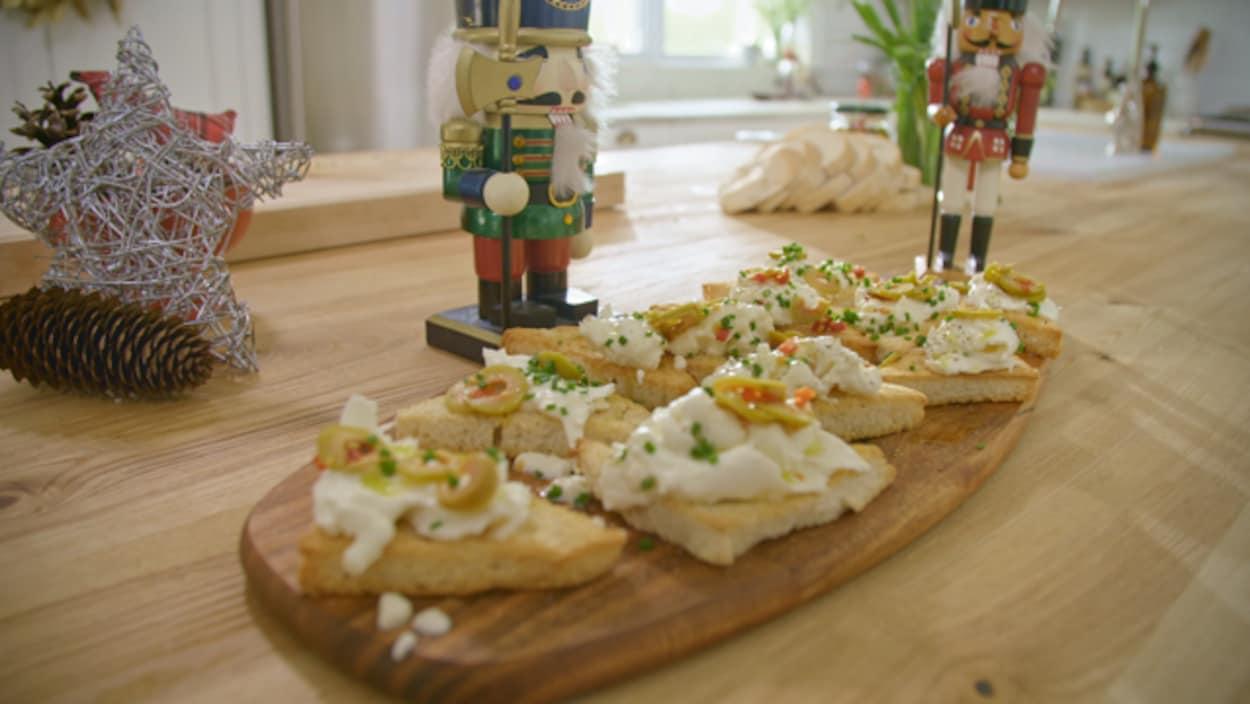 Des triangles à la burrata et aux olives vertes farcies disposés sur une planche.