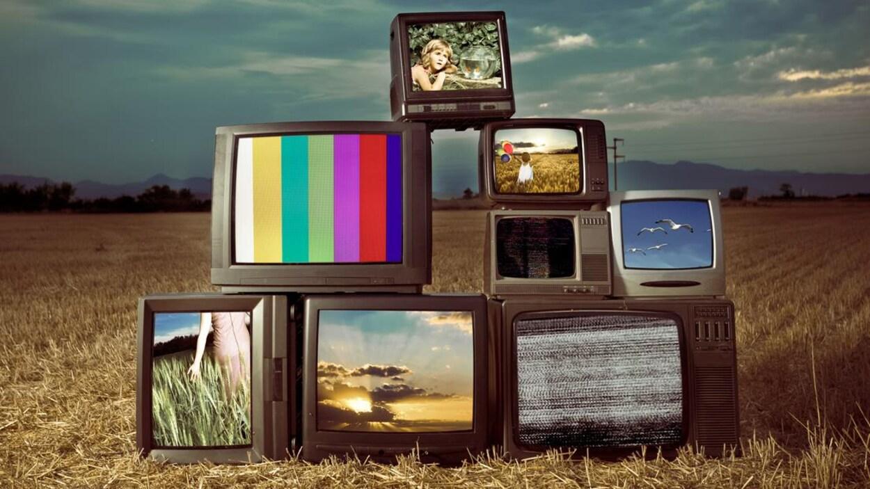 Huit télévisions empilées les unes sur les autres en forme de pyramides dans un champ de blé.