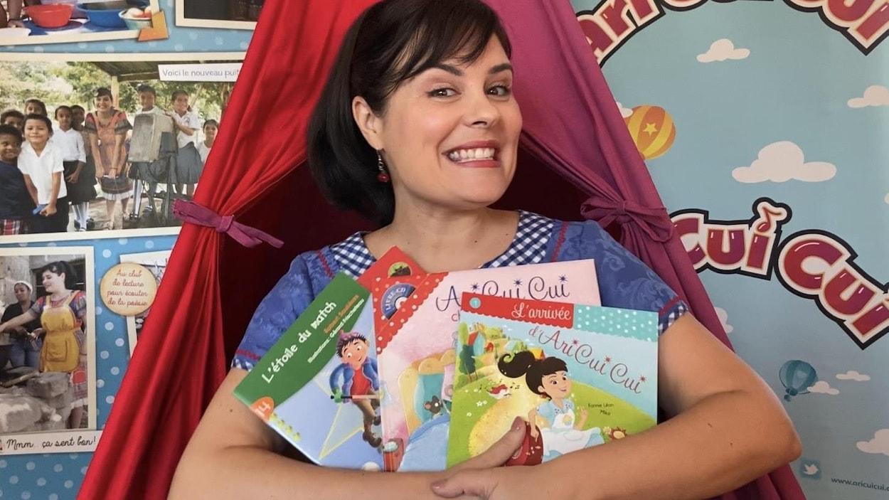 Elle sourit en montrant trois contes qu'elle va lire aux enfants