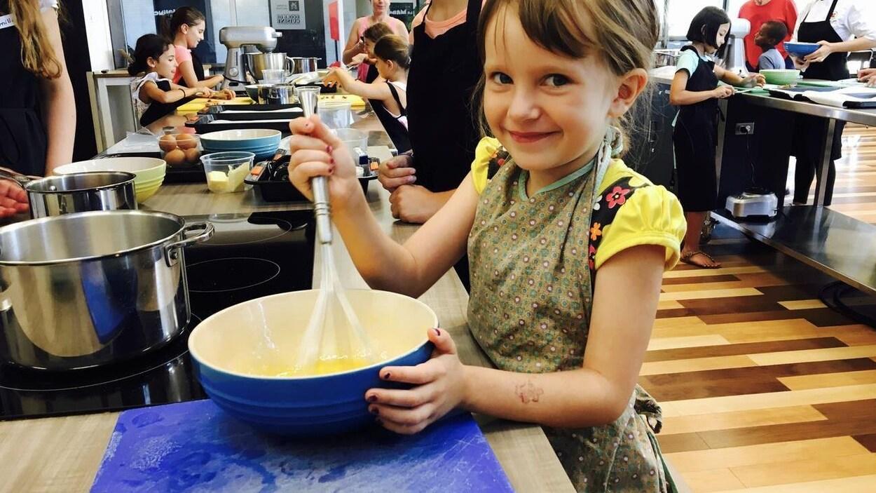 Une fillette sourit en brassant des oeufs dans un bol