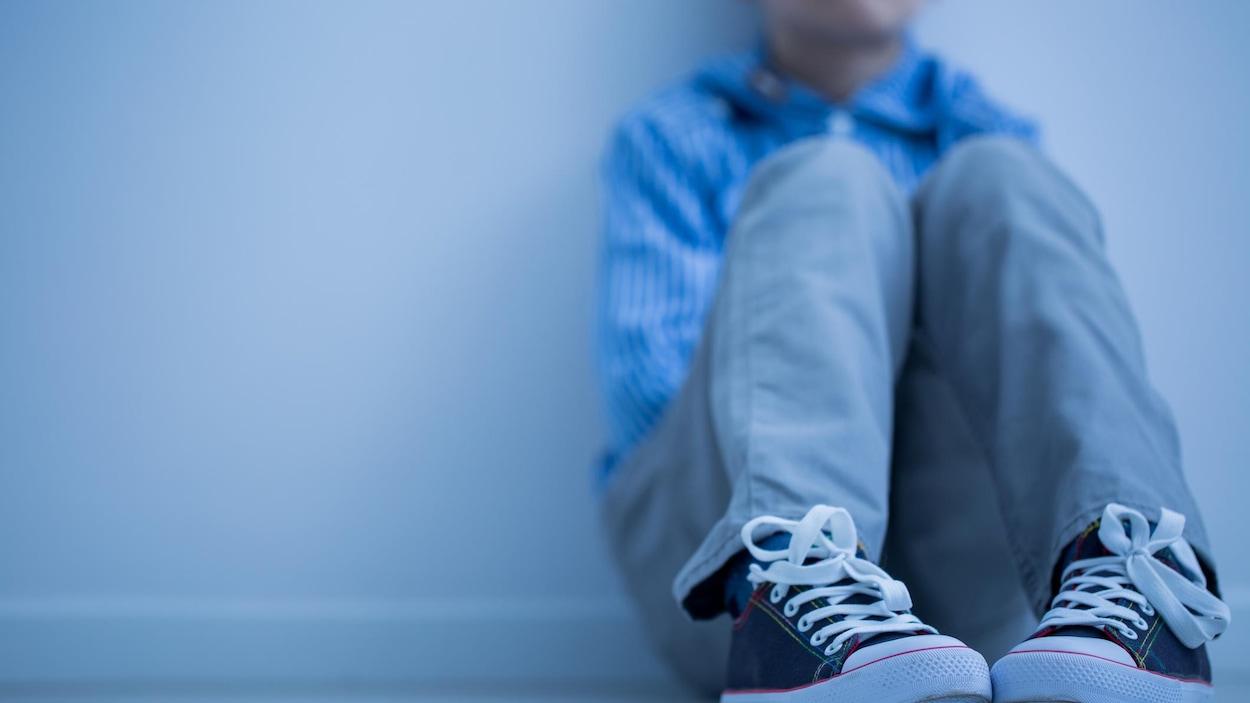 Un garçon à l'air triste est assis, seul, par terre.