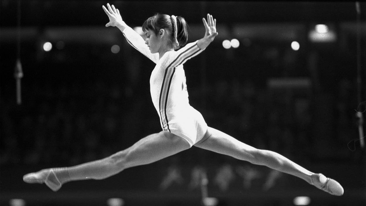 La gymnaste Nadia Comaneci saute en faisant le grand écart.