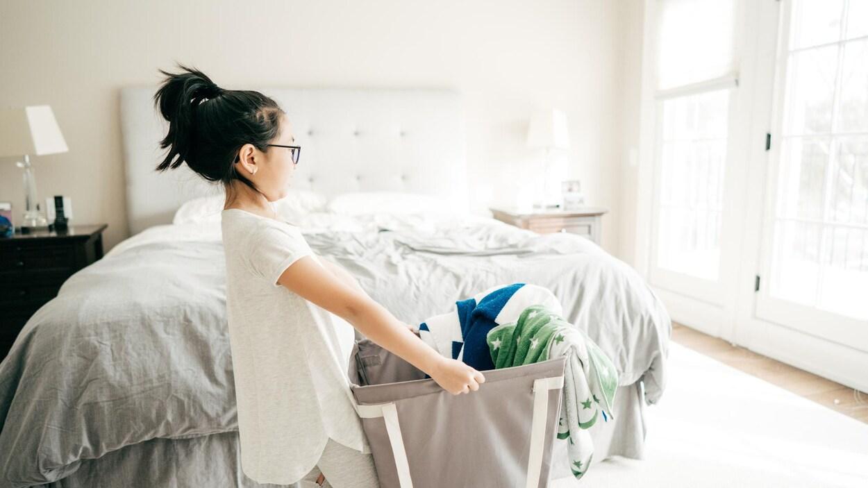 Une petite fille transporte un panier de lessive dans une chambre.