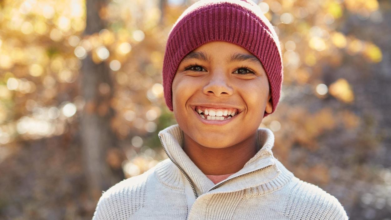 Il sourit et porte un bonnet et un pull. Nous sommes en automne.