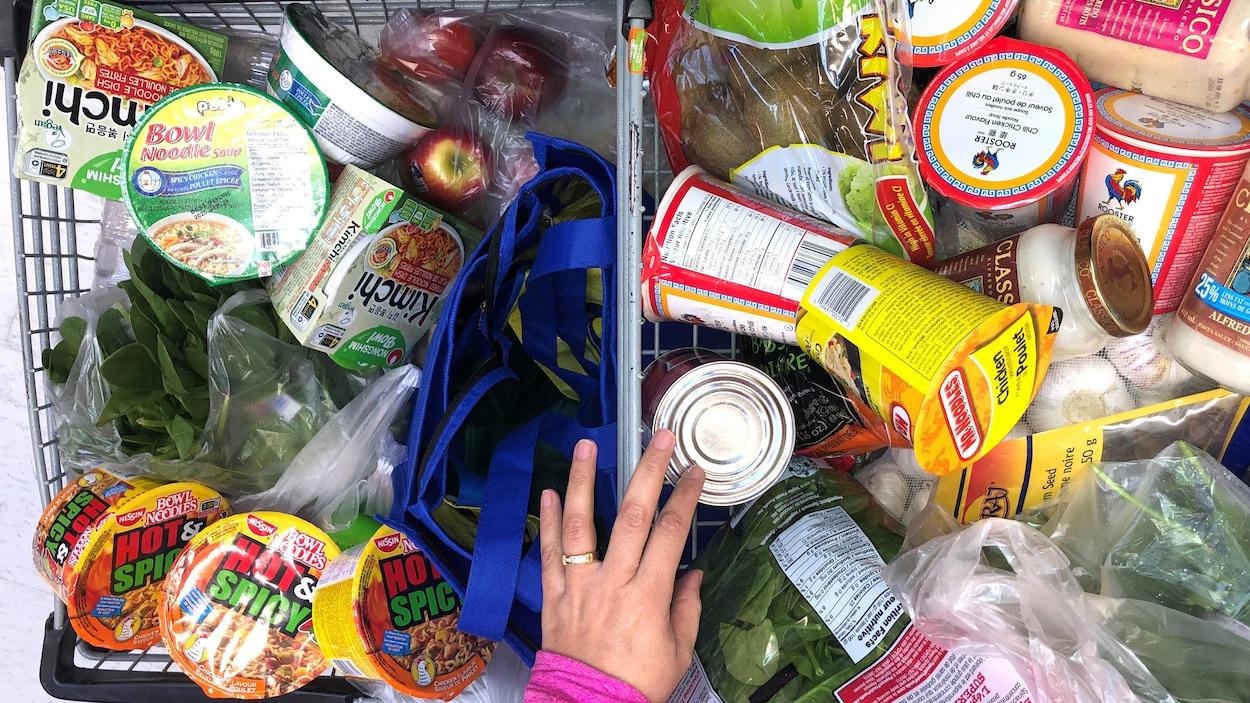 Un client remplit son panier d'épicerie de nourriture.