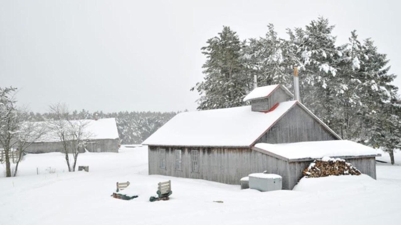 Un bâtiment en bois est recouvert de neige.