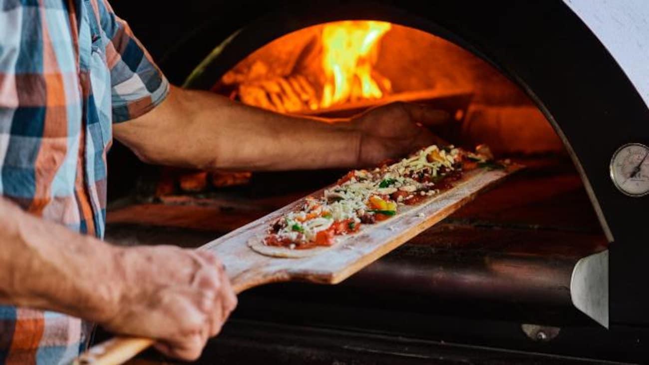 Un cuisinier s'apprête à mettre la pizza dans le four à bois.