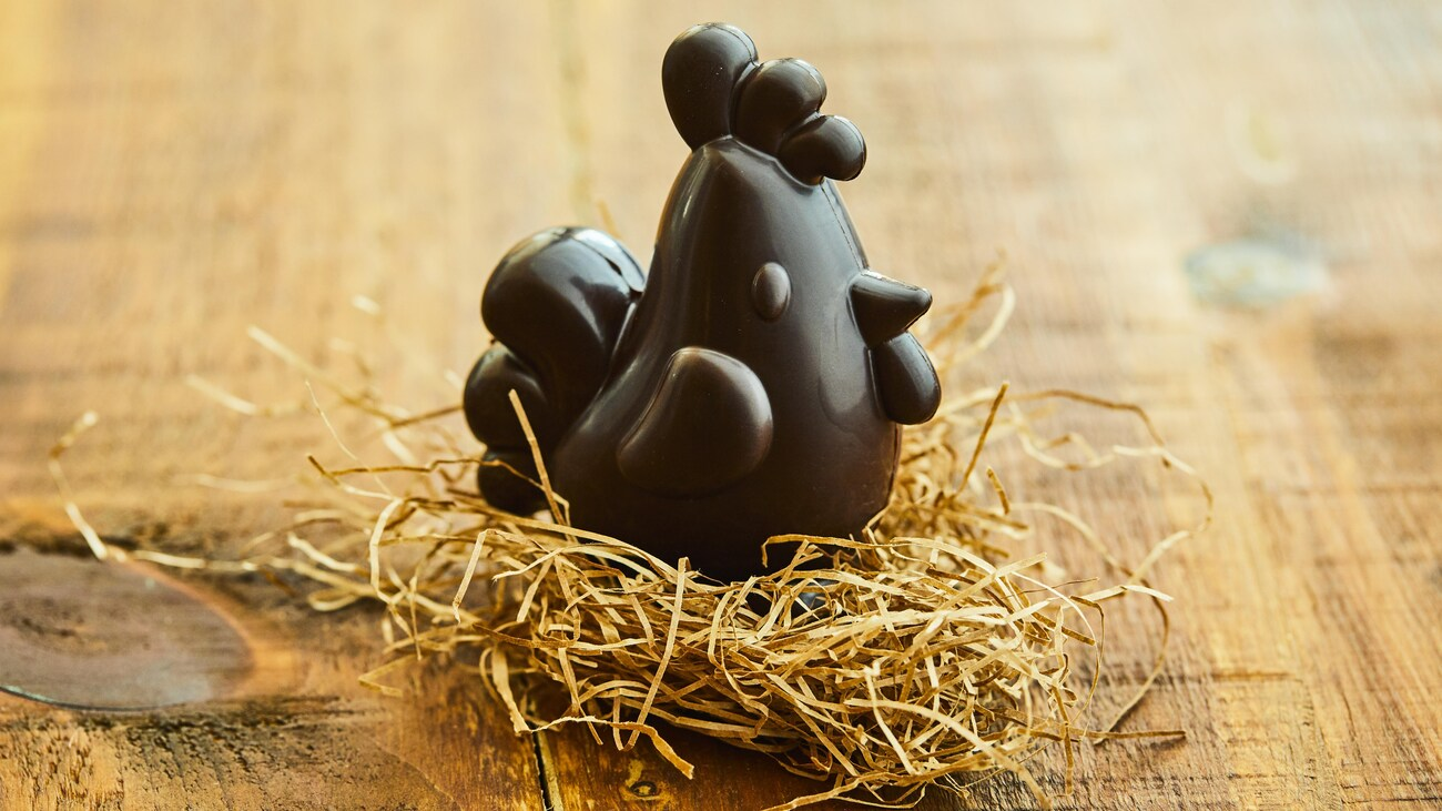 Poule en chocolat noir sur un nid de paille.