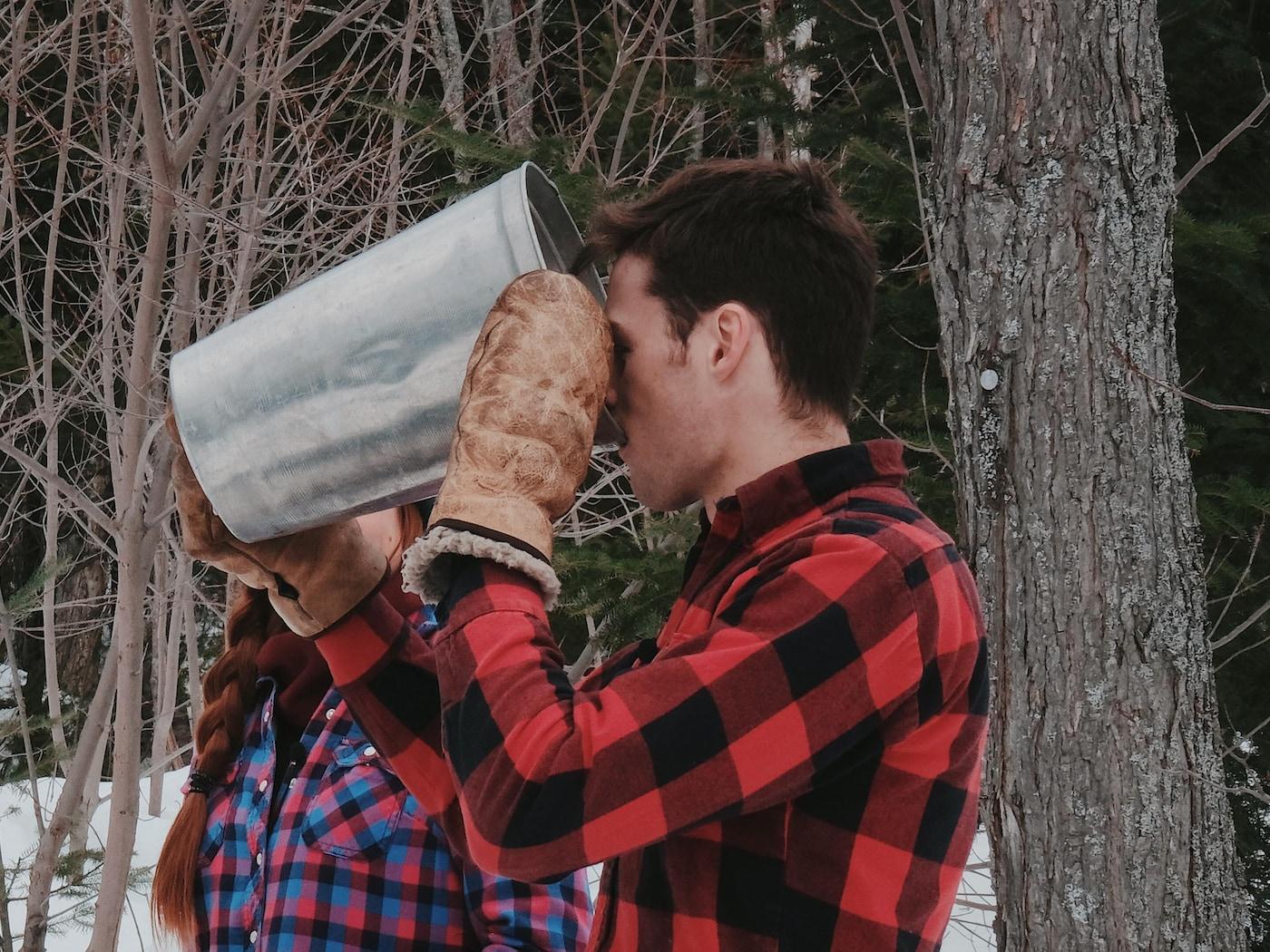 Nicolas boit de l'eau d'érable à même une chaudière