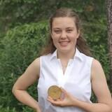 Laurissa Brousseau porte une chemise blanche et tient sa médaille.