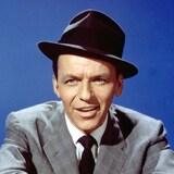 Frank Sinatra sur fond bleu, souriant, vêtu d'un chapeau melon et d'un élégant costume cravaté