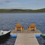 Deux chaises Adirondack se trouvent sur le quai d'un lac en Haute-Mauricie. Deux chaloupes flottent de chaque côté.