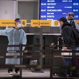 Des voyageurs font la file près d'un employé de l'aéroport portant un masque, une visière et une tenue protectrice.